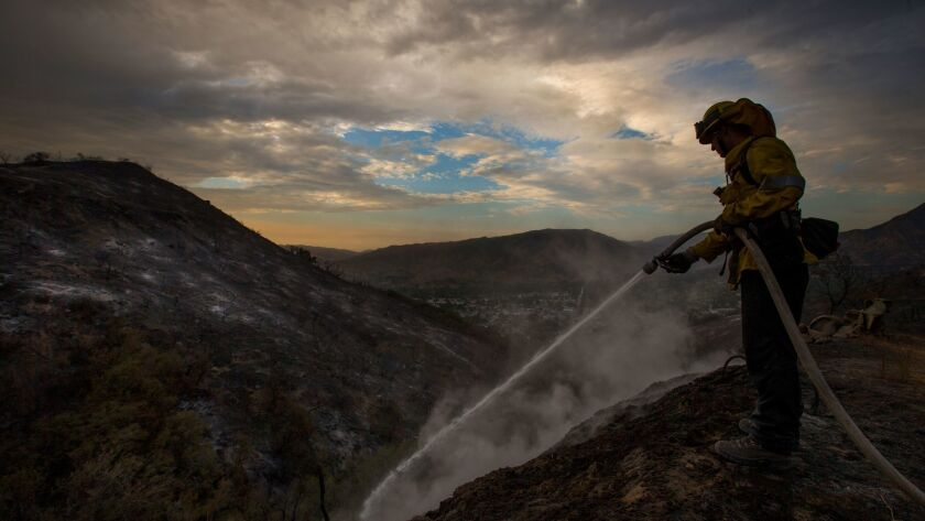 Los Angeles County firefighter Kevin Sleight extinguishes hot spots while battling the La Tuna fire.