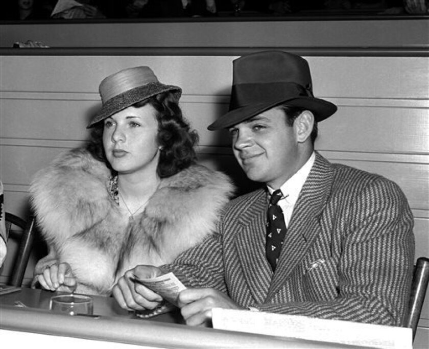 FILE - In this May 30, 1939 file photo, actress Deanna Durbin sits with Vaughn Paul in the clubhouse of Hollywood Park in Los Angeles. Paul was Durbin's first husband. Durbin, the internationally famous child star from Hollywood's Golden Age who brought her pure soprano voice and natural, girl-next-door looks to nearly 30 movies, died in April 2013. Family friend Bob Koster, whose father directed six of Durbin's films, tells The Associated Press on Wednesday May 1, 2013 that she died at age 91 i