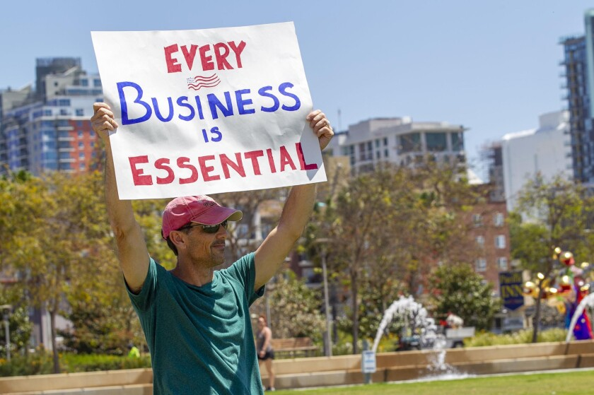 """Brian Tinney, an IT contractor, is himself working but worried about all of the small businesses that are being forced to stay closed even though he thinks they could be open and working smart to avoid the spread of COVID-19. About 50 people participated in a protest organized by the Facebook Group """"Liberate San Diego"""" at the corner of Harbor Drive and Grape Street near the County Administration Building on April 24, 2020, urging elected officials to start a reopening of the economy."""