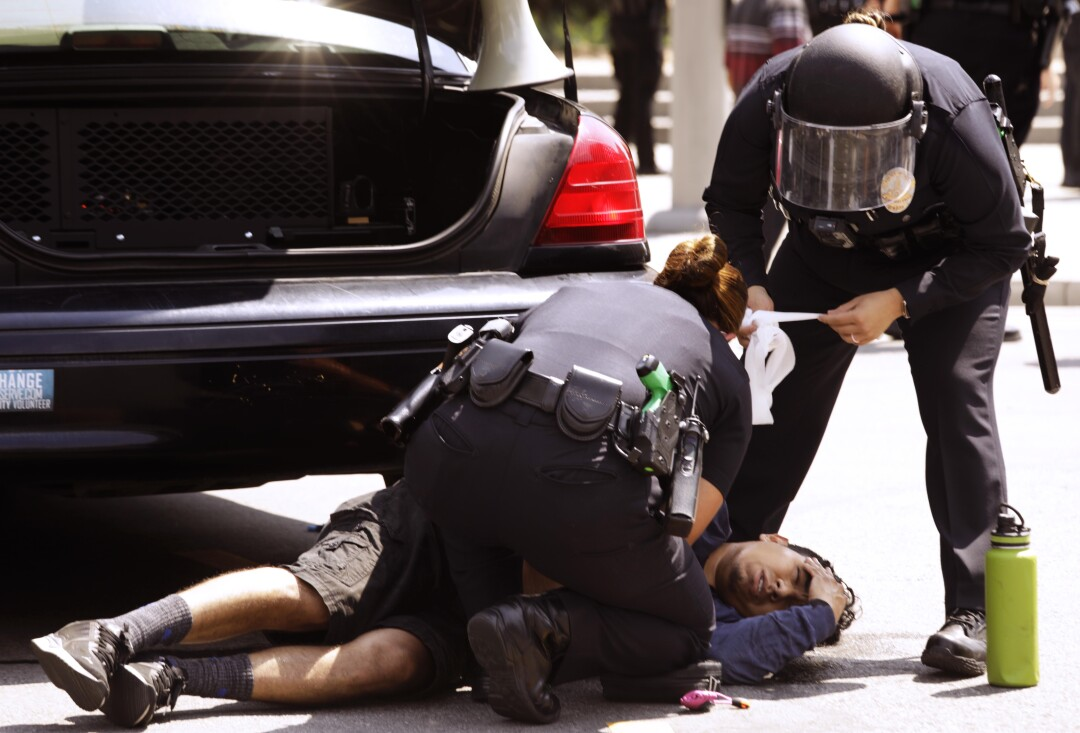 A Los Angeles police officer tries to stop the bleeding of a man who was stabbed.