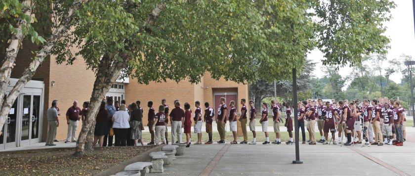 Members of the Salem High school football team arrive for a visitation for WDBJ-TV cameraman Adam Ward at the school in Salem, Va., Monday, Aug. 31, 2015.