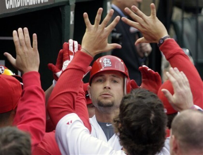 St. Louis Cardinals' Matt Holliday celebrates with teammates in the dugout after hitting a solo home run during the eighth inning of a baseball game against the San Diego Padres on opening day, Thursday, March 31, 2011, in St. Louis. The Padres beat the Cardinals 5-3 in 11 innings. (AP Photo/Tom Ga