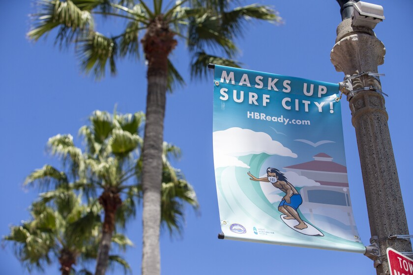 """New signs that say """"Masks Up, Surf City"""" line Main Street in Huntington Beach on Tuesday."""