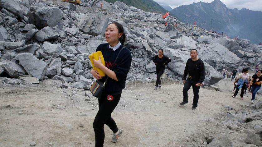 A woman brings paper offerings to the landslide site in Xinmo.