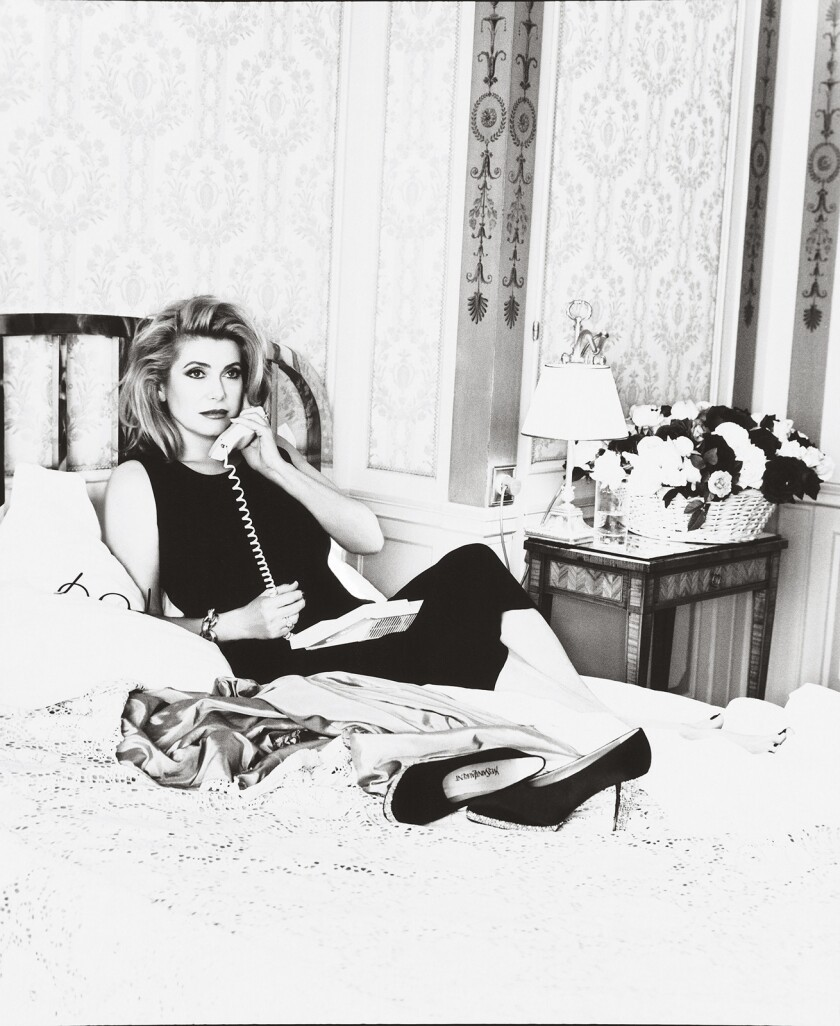 Catherine Deneuve lounges in an opulent hotel room in a 1995 portrait of the French actress.
