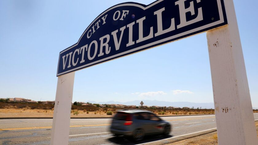 A car drives past a roadside sign for the city of Victorville