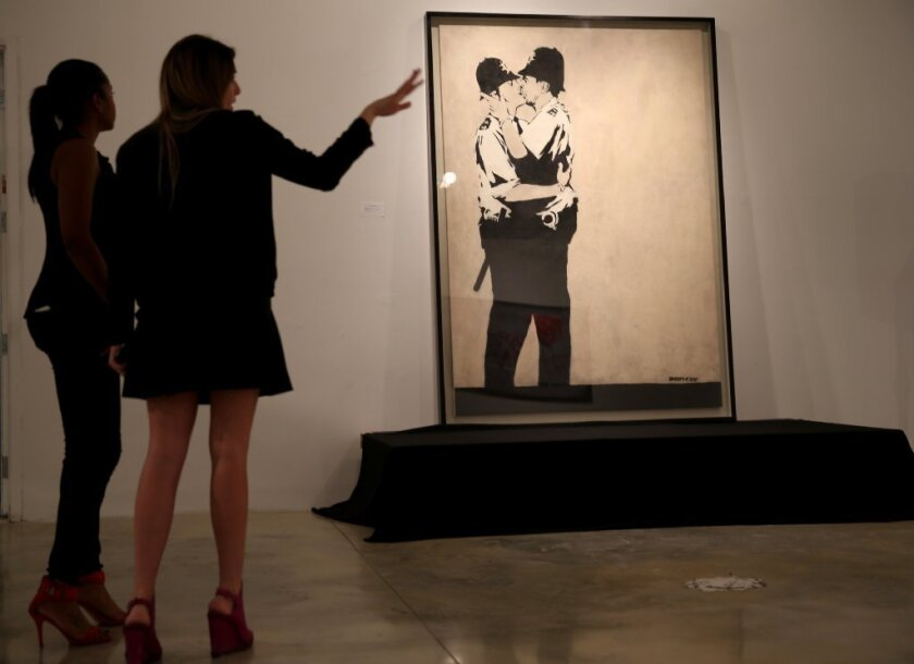 """Kissing Coppers"" by the street artist Banksy was sold on Tuesday at a Miami auction of street art."