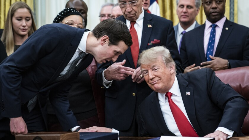 Jared Kushner confers with President Trump at a White House signing ceremony in December 2018.