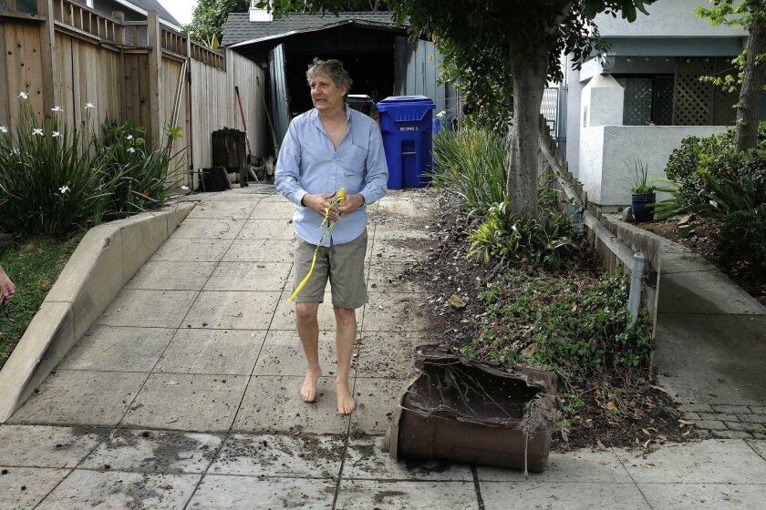 A morning fire in a garage next to a Herbert Street home was extinguished before flames could spread to other structures. Tim Gahagan, who lost many belongings in the blaze alleged to be arson, walks down his driveway near a melted garbage container.