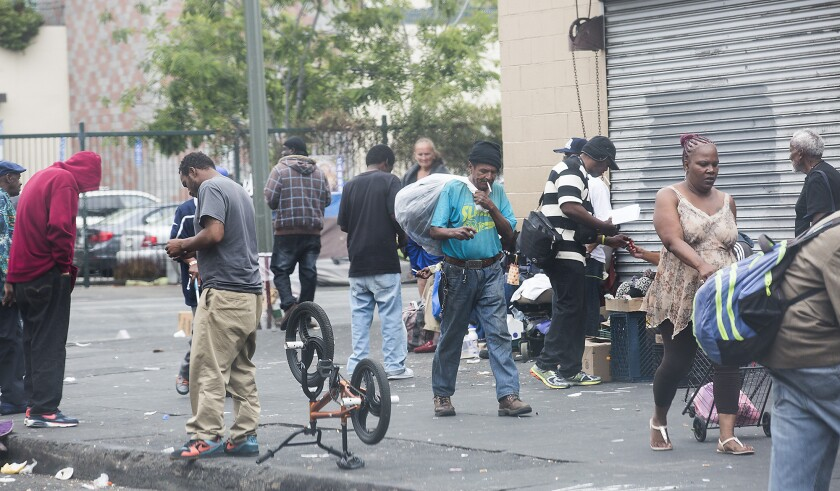 People gather on Skid Row corner at San Pedro Ave. and 5th Street in Los Angeles, Calif., on May 4.