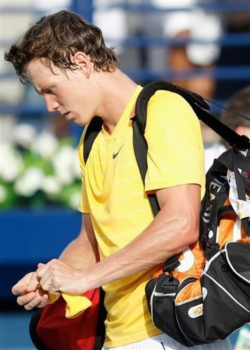 Tomas Berdych of Czech Republic leaves the court after he retired due to medical condition during the match opposite Serbia's Novak Djokovic during the semi finals of the Emirates Dubai ATP Tennis Championships in Dubai, United Arab Emirates Friday, Feb. 25, 2011.(AP Photo/Nousha Salimi)