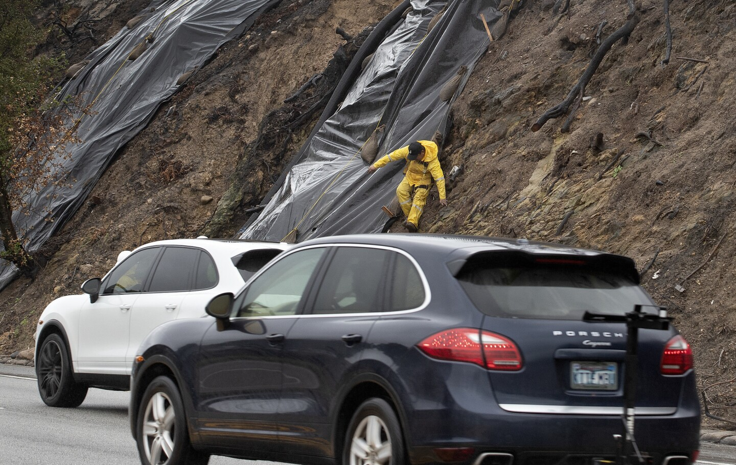 Rolly Chinan makes his way down a hillside after securing a tarp on Pacific Coast Highway in Malibu.
