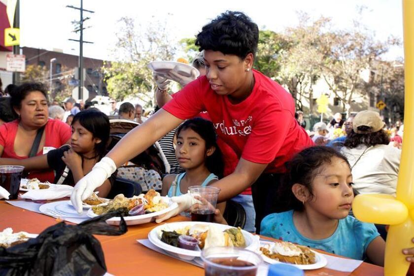 Una voluntaria entrega un plato durante una comida para personas sin hogar. EFE/Archivo