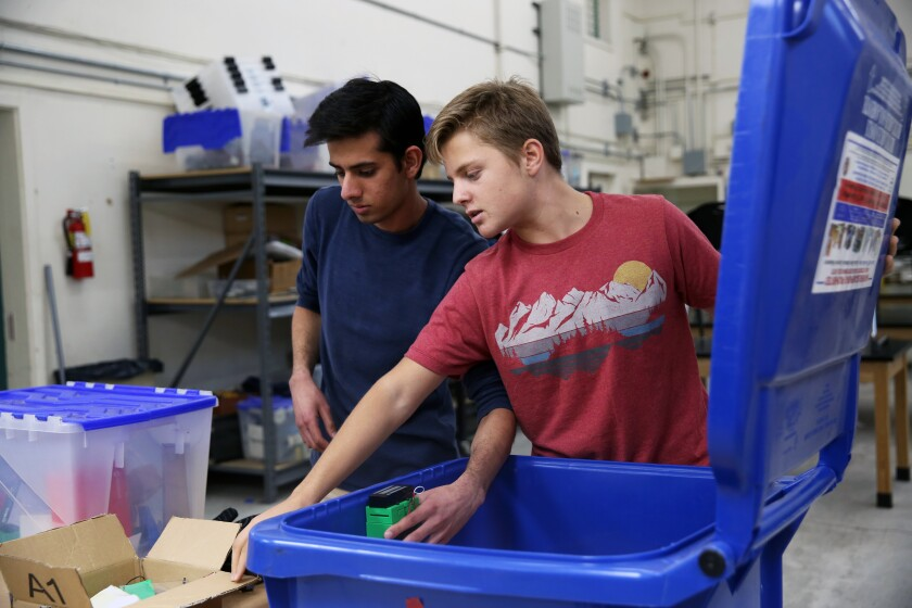 Akshat Bansal, 17, left, and William Bacon, 16, demonstrate a work in progress to minimize trash from blowing out from bins in their communities.
