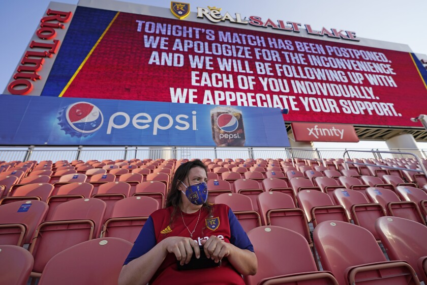 A fan sits in the stands after the scheduled game between Real Salt Lake and LAFC was postponed.