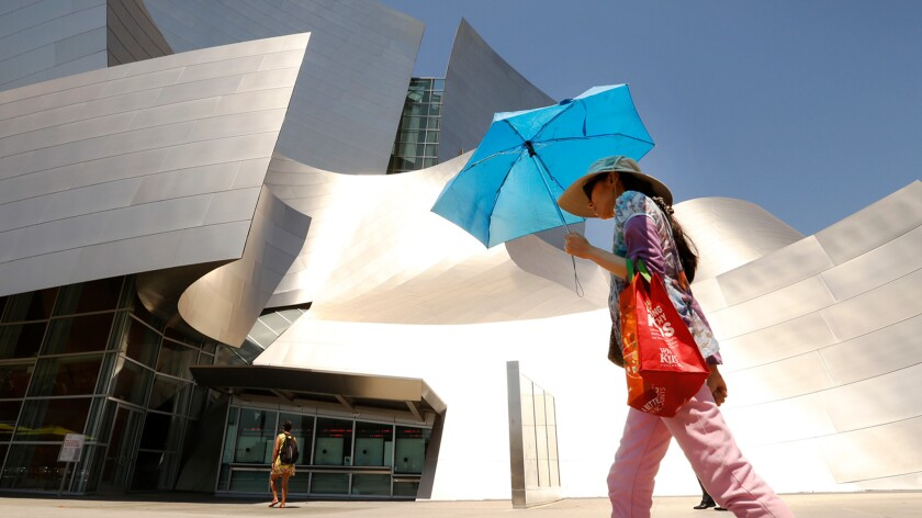 A woman shields herself from the sun in downtown Los Angeles.