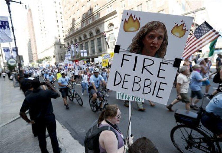 Una partidaria del senador independiente por Vermont Bernie Sanders, alza un cartel pidiendo la destitución de Debbie Wasserman Schultz, presidenta del Comité Nacional Demócrata, el domingo 24 de julio de 2016 en FIladelfia. (AP Foto/Alex Brandon)