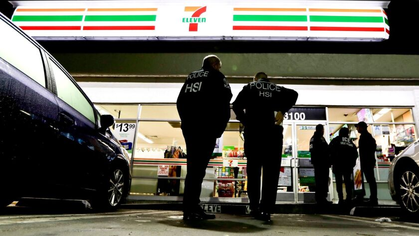 U.S. Immigration and Customs Enforcement agents serve an employment audit notice at a 7-Eleven conve