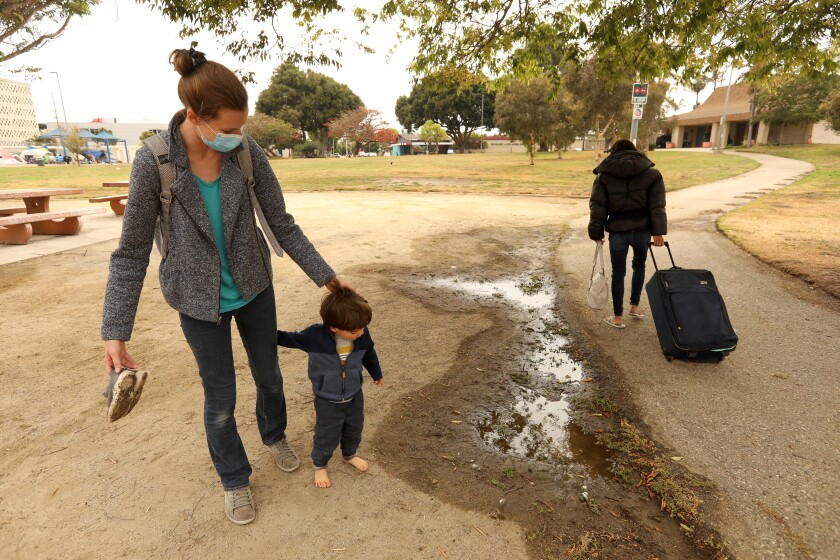 Stephanie Popescu and her son head to the playground as a homeless woman walks by in Westchester Park.
