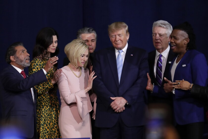 FILE - In this Friday, Jan. 3, 2020 file photo, faith leaders pray with President Donald Trump during a rally for evangelical supporters at the King Jesus International Ministry church in Miami. The conservative evangelical Christians who helped send Trump to the White House four years ago stuck by him again in 2020. But even if Trump doesn't get a second term, some conservative Christians see reasons to celebrate in this year's election results. (AP Photo/Lynne Sladky)