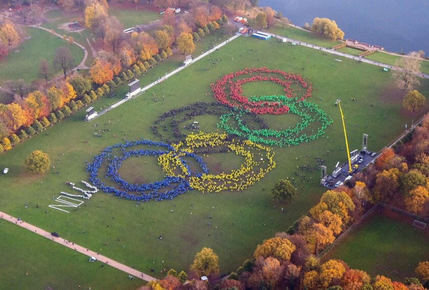 "An aerial view shows thousands of  people wearing colorful ponchos to  form  the Olympic rings to support Hamburg's bid for the Olympics 2024,  in a park in Hamburg, Germany, Sunday Nov. 8,  2015. At left, protesters against Hamburg's Olympic bid laid  the word  ""NO"" next to the giant Olympic logo,"