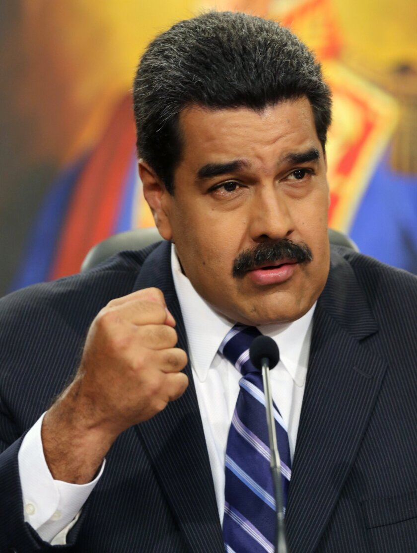 Venezuela's President Nicolas Maduro speaks during a press conference at Miraflores Presidential Palace in Caracas, Venezuela, Tuesday, Dec. 30, 2014. Venezuela's socialist government Tuesday confirmed the economy fell into a deep recession this year but blamed the slump on opponents trying to sabo