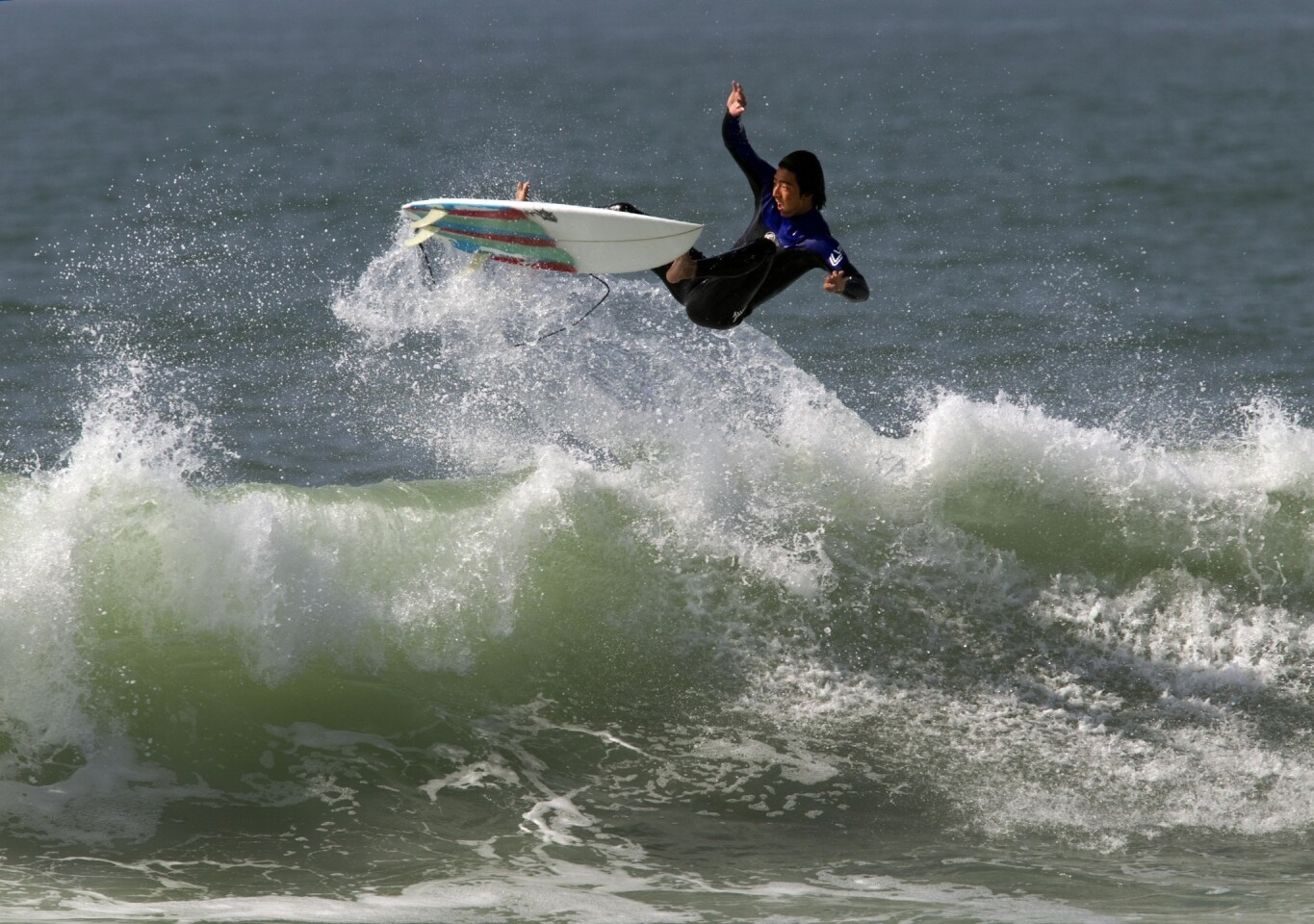 A surfer goes airborne high over a big wave at the Newport Beach jetties Wednesday.