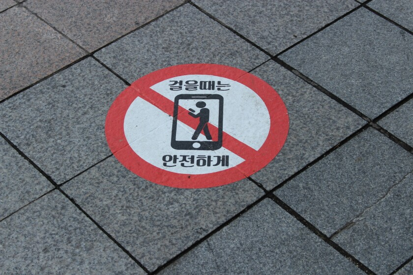 """Pedestrians in Seoul are reminded to look where they are going. The Korean text translates as """"Walk safely."""""""