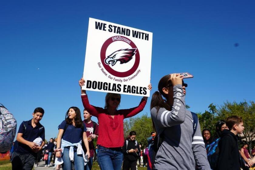 Decenas de personas participan en una manifestación convocada por los estudiantes de la escuela secundaria Marjory Stoneman Douglas el miércoles 14 de marzo de 2018, en Parkland (EE.UU.). Decenas de miles de estudiantes salieron hoy a las calles en todo Estados Unidos o se concentraron en sus escuelas en señal de dolor por la matanza perpetrada el pasado 14 de febrero en un instituto de Parkland, en el sur de Florida, y en demanda de un mayor control en la venta de armas. EFE/Archivo