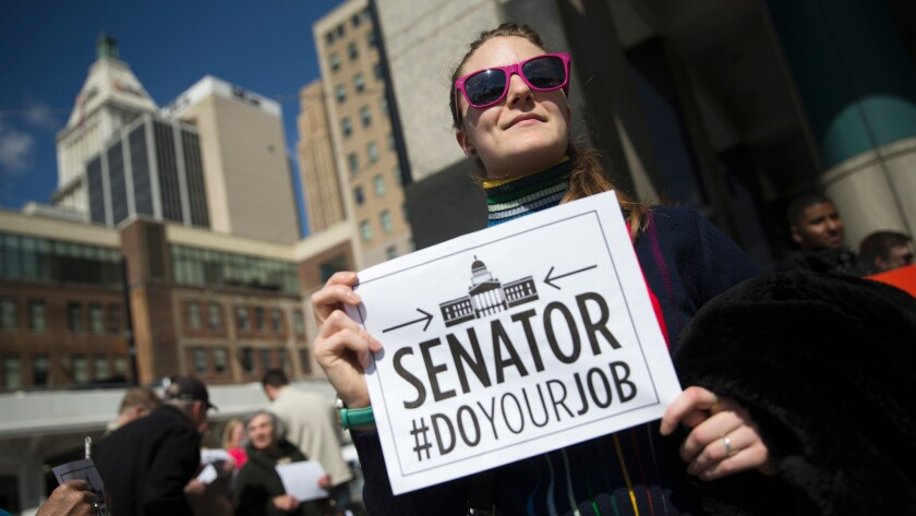 A picketer stands outside the office of Sen. Rob Portman, R-Ohio, in Cincinnati on March 21. The protest was part of a group of rallies around the country targeting Republican senators who opposed confirmation hearings for the president's Supreme Court nominee Merrick Garland.