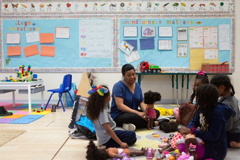 Renee Curry, a therapist, leads a group of girls during a doll play session at Crete Academy in South Los Angeles in March.