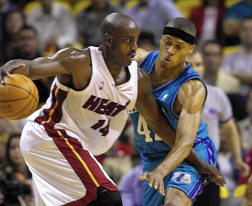 Miami's Anthony Mason, left, drives against Charlotte's P.J. Brown in an NBA game in 2001. Mason, a rugged power forward who was a defensive force throughout his career, has died at the age of 48.