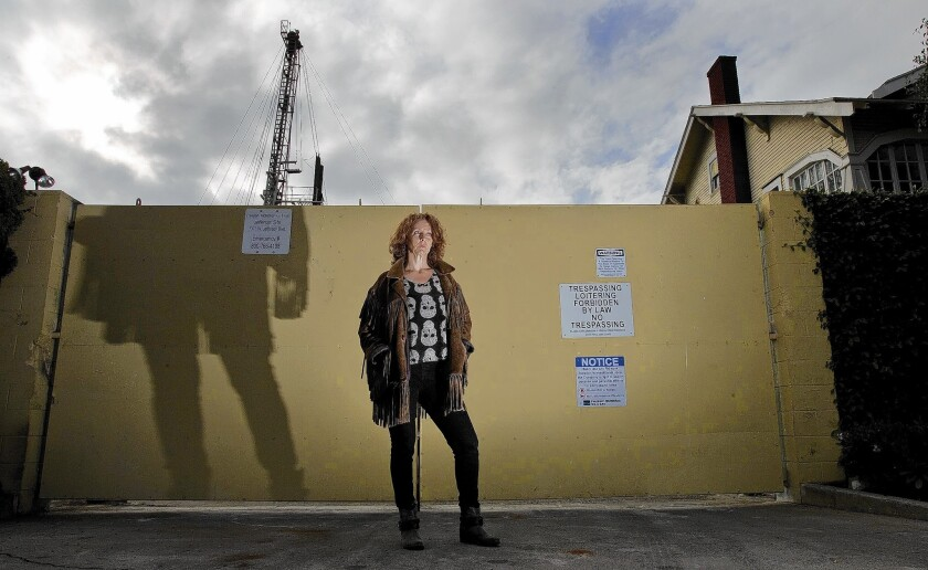 "DonnaAnn Ward, founder of Cowatching Oil L.A., stands at a drilling site at Jefferson and Budlong avenues. She hopes an L.A. ban on ""well stimulation,"" including fracking, will discourage oil and gas companies from drilling."