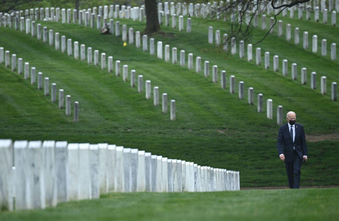 President Biden walks among gravestones at Arlington National Cemetery.
