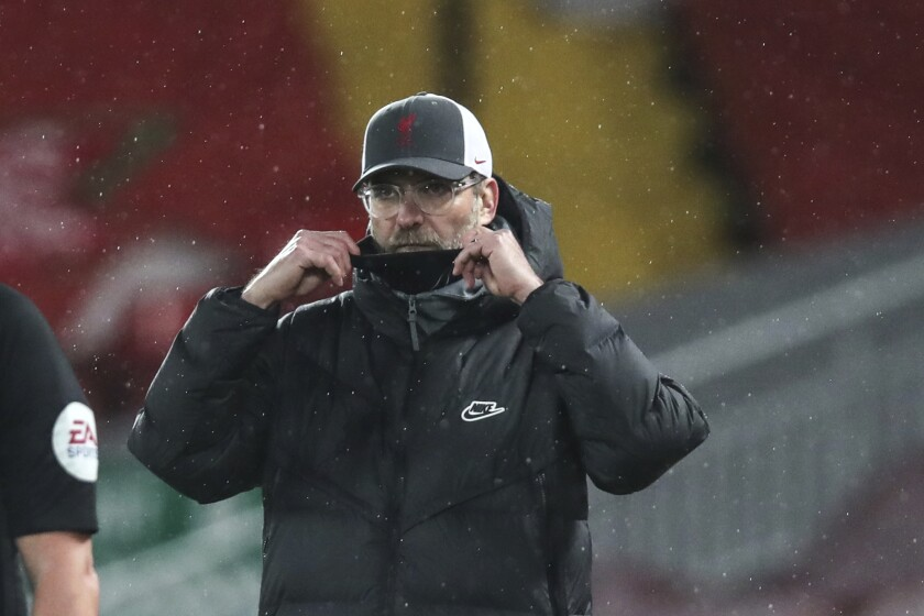 Liverpool's manager Jurgen Klopp fixes his protective mask during the English Premier League soccer match between Liverpool and Brighton at Anfield stadium, in Liverpool, England, Wednesday, Feb. 3, 2021.(Clive Brunskill/Pool via AP)