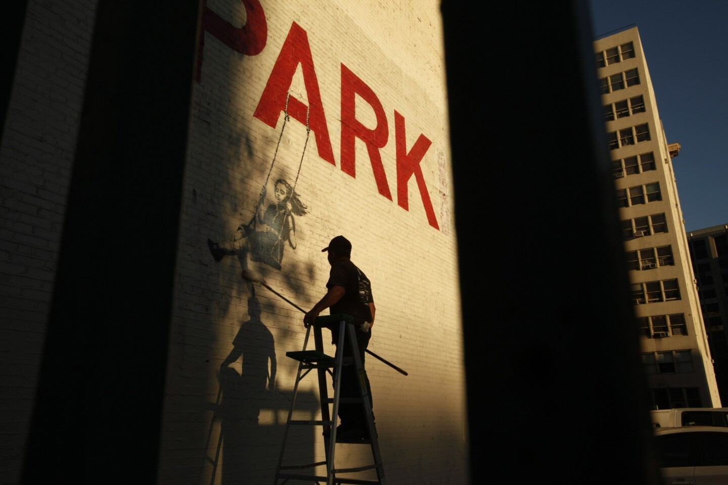 "A young girl swings from the word ""PARK"" within Banksy's downtown Los Angeles mural. But an additional ""ING"" has been faded out by Banksy, turning the word ""PARKING"" into ""PARK."" Just down the block from this area, a downtown resident group is looking to find a little more than $6 million to transform a parking lot into a community park with a playground."