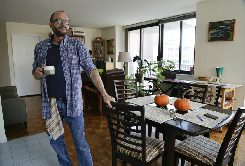 In this photo taken on Oct. 16, 2014 photo, Jim Albaugh talks about his living arrangements in the New York apartment he shares with two roommates. Albaugh could be thought of as just one of the working poor, untold millions in the baby boomer generation who are not prepared for retirement. But he represents something more as one of thousands of gay and lesbian baby boomers confronting a retirement of greater financial hardship than his straight peers. (AP Photo/Julie Jacobson)