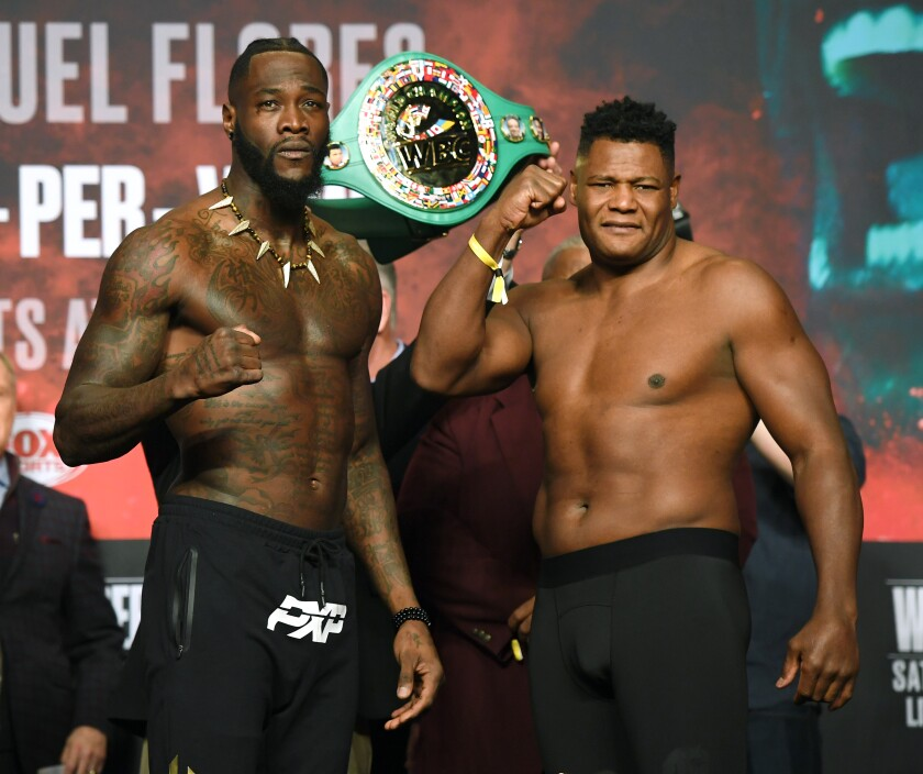 WBC heavyweight champion Deontay Wilder, left, and Luis Ortiz pose during their official weigh-in at MGM Grand Garden Arena on Friday in Las Vegas.