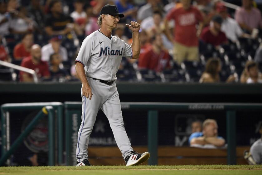 Don Mattingly, manager de los Marlins de Miami, camina hacia el montículo para ordenar la llegada de un nuevo pitcher al juego del lunes 19 de julio de 2021, ante los Nacionales de Washington (AP Foto/Nick Wass)