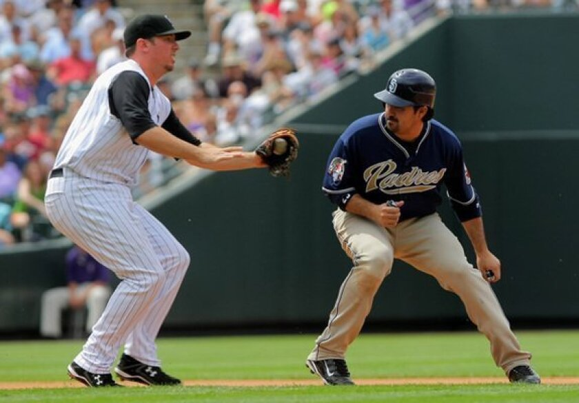 Adrian Gonzalez is caught trying to steal third and is tagged out by Rockies third baseman Garrett Atkins in the seventh inning Sunday. (Photo by Doug Pensinger/Getty Images)