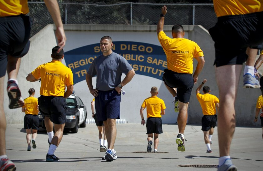 Geoff DeCesari, recruit training officer at the San Diego Regional Public Safety Training Institute in Mira Mesa at Miramar College, watches San Diego police and sheriff's recruits during morning physical training.