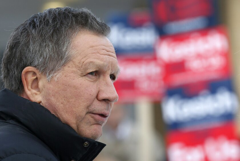 Republican presidential candidate, Ohio Gov. John Kasich visits a polling station at the high school, Tuesday, Feb. 9, 2016, in Manchester, N.H. as voters cast their ballots for the first in the nation presidential primary.  (AP Photo/Jim Cole)