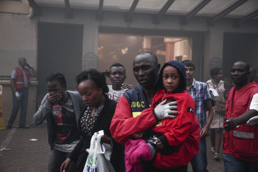 People escape from a fire said to have been started by gunmen inside the Westgate shopping mall in Nairobi, Kenya.