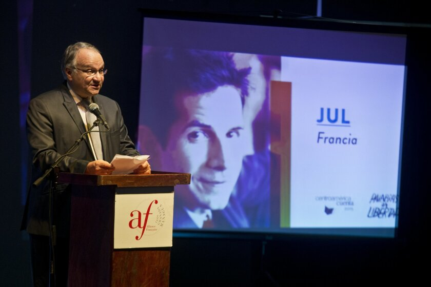 """French ambassador in Nicaragua, Antoine Joly speaks next to a projection with a portrait of French cartoonist Jul during the inauguration ceremony of the """"Centroamerica Cuenta"""" writer's meeting in Managua, Nicaragua, Tuesday, May 19, 2015. Jul was refused entry into Nicaragua by immigration authorities as he arrived to participate in the tribute to Charly Hebdo. (AP Photo/Esteban Felix)"""