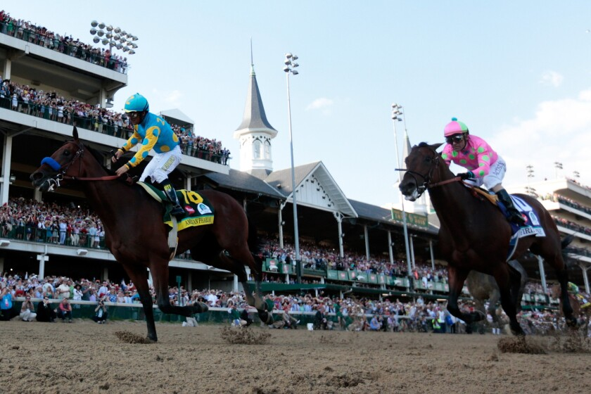 American Pharoah, with jockey Victor Espinoza aboard, wins the 141st Kentucky Derby by a length over Firing Line and jockey Gary Stevens.