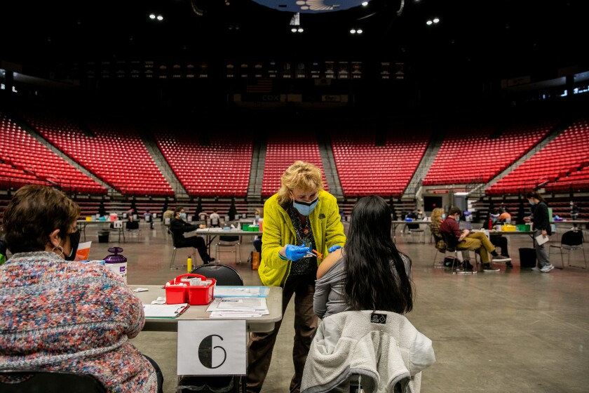 A nurse dressed in a yellow jack gives a vaccine shot to a woman in an  arena.