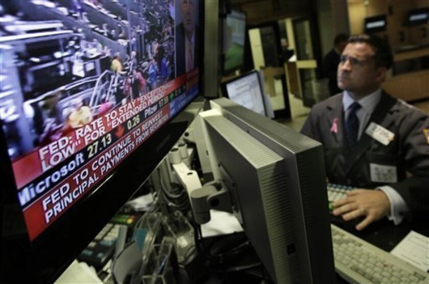 """The interest rate decision of the Federal Reserve is seen on a television screen at the post of specialist Paul Cosentino, on the floor of the New York Stock Exchange Wednesday, Nov. 3, 2010. The Fed pledged to hold its key interest rate at a record low near zero for """"an extended period."""" (AP Photo/Richard Drew)"""
