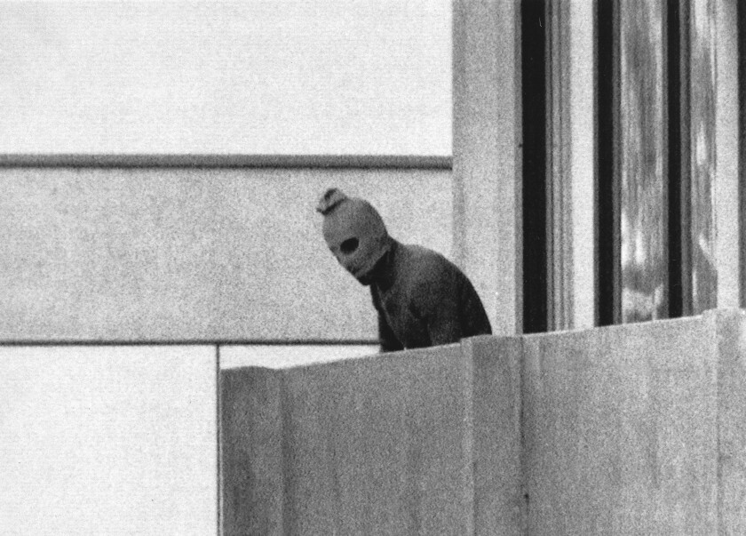 FILE - In this Sept. 5, 1972 b/w file photo, a member of the Arab Commando group which seized members of the Israeli Olympic Team at their quarters at the Munich Olympic Village appears with a hood over his face on the balcony of the village building where the commandos held members of the Israeli team hostage. The presidents of Germany and Israel will jointly commemorate the 45th anniversary of the death of 11 Israeli athletes killed by a Palestinian militant group during the 1972 Munich Olympics. (AP Photo/Kurt Strumpf,file)