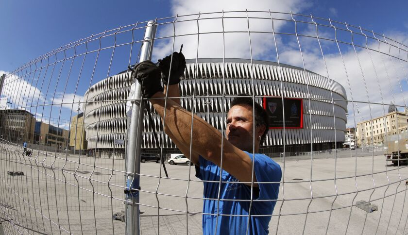 A worker erects a fence around San Mames stadium in order to separate fans in Bilbao, Spain, in 2018.