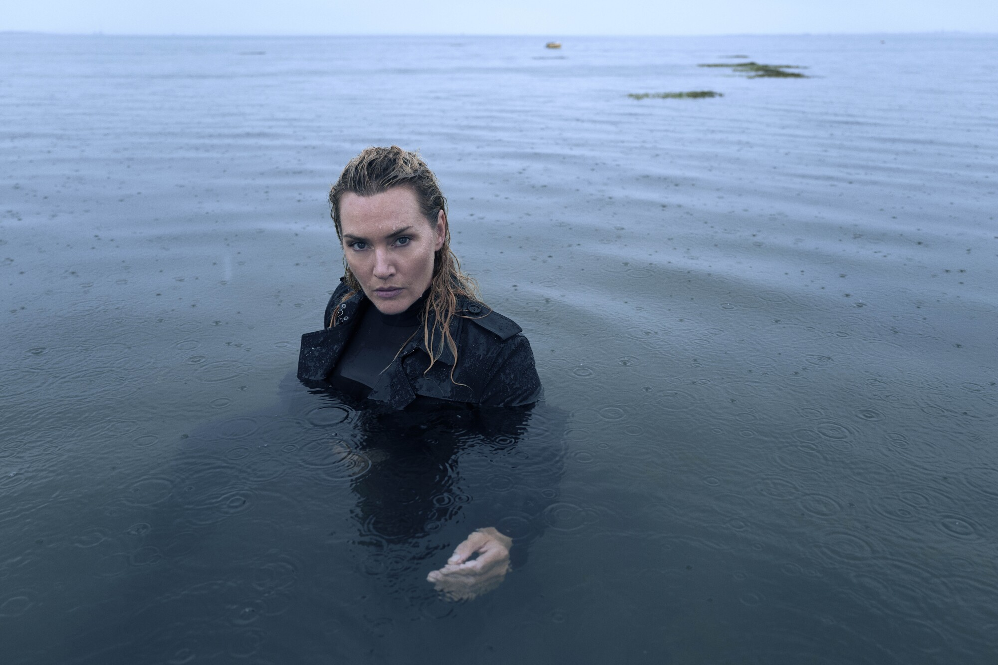 A fully dressed Kate Winslet immerses herself in a body of water in the rain.